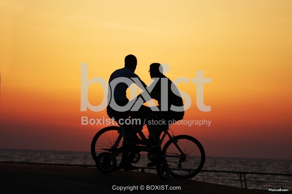 Two Bicycle Riders at Sunset
