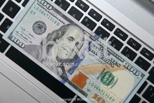 Hundred Dollar Bill on Top of Computer Keyboard