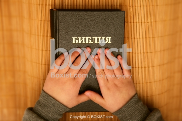 Hands On Top Of Russian Bible Book