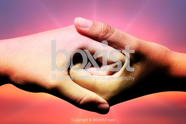 Two Hands Shake Against Colorful Background
