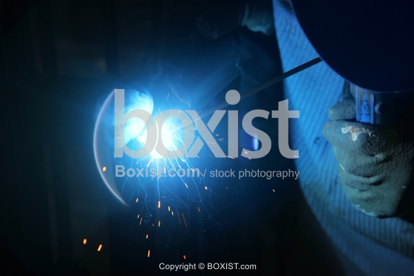 Worker Welding Metal With Bright Light