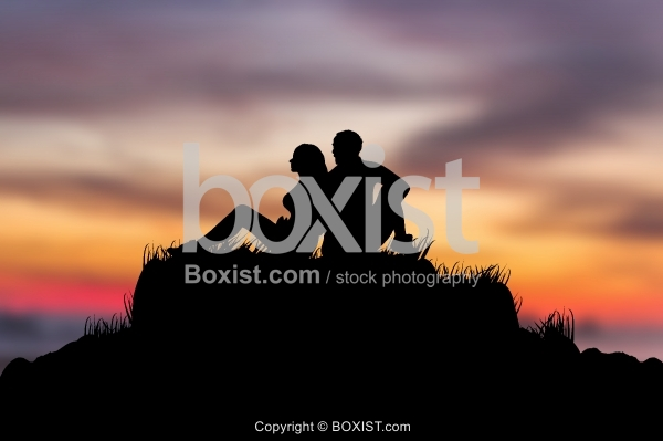 Couple Silhouette Sitting Together At Sunset Time
