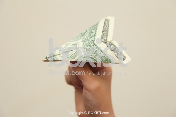 Flying Paper Plane With Dollar Bill Holding In Hand